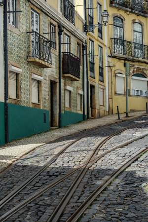 Lisbon high slope street with rail and tile facade