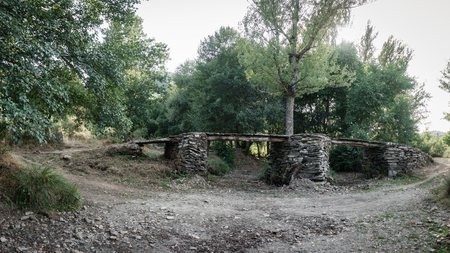 Old antique stone bridge over dry river