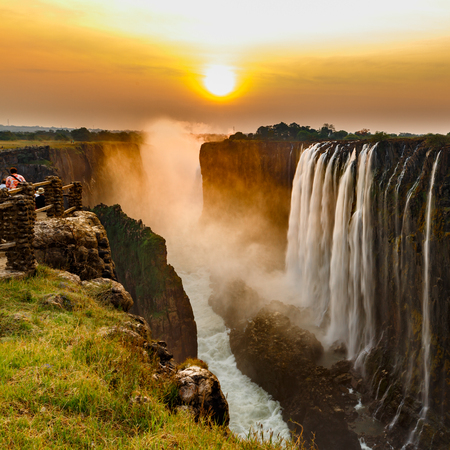 Victoria falls sunset with orange sun and tourists Banco de Imagens - 109113717