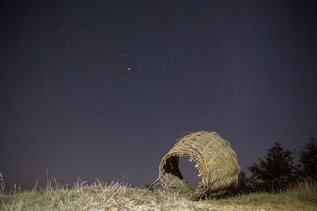Old wicker basket with startrail in the background