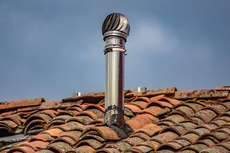 Aluminum chimney over old red tile roof Stok Fotoğraf