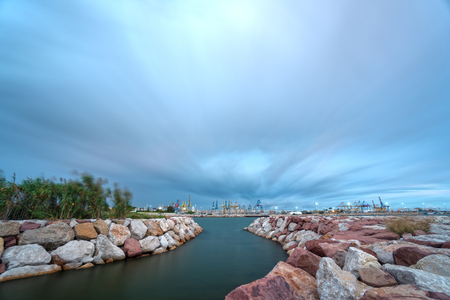 Canal with huge stones and commercial port with cranes, long exposure Reklamní fotografie