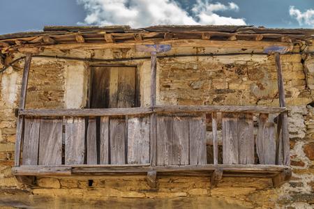 Old vintage run-down wooden balcony, stone facade