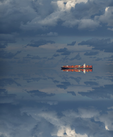 Large cargo ship over the horizon at dusk with reflection