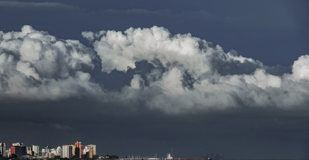 Long shot of skyscrappers near sea with stormy clouds