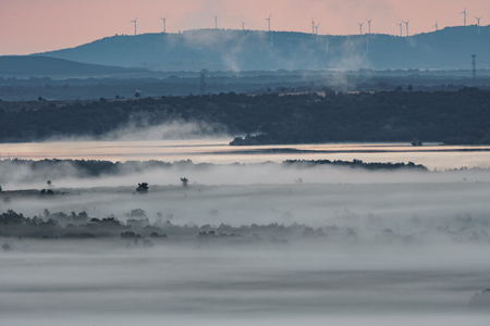 Foggy sunrise in the country with dam and windmills in the background Imagens