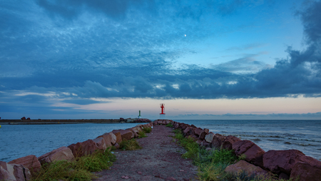 Marina mouth entrance and lighthouse at dusk in breakwater Banco de Imagens