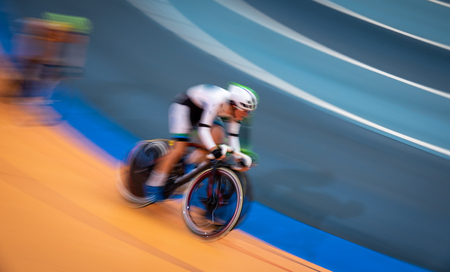 Blurred motion of fast cyclist competing indoor Stock Photo - 114635507