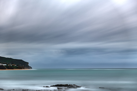 Ultra long exposure of ocean with stormy clouds and cape Stock Photo