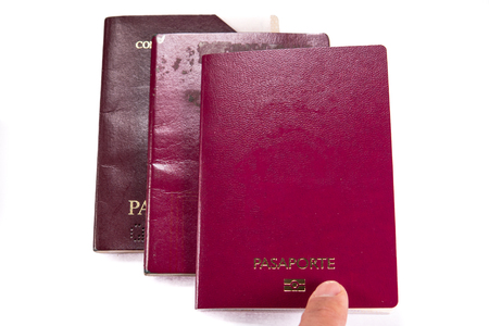 Finger pointint new blank passport over old expired ones Stockfoto