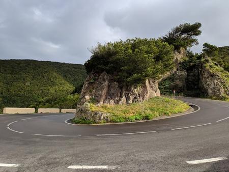 U-shape mountain curved road against cloudy sky