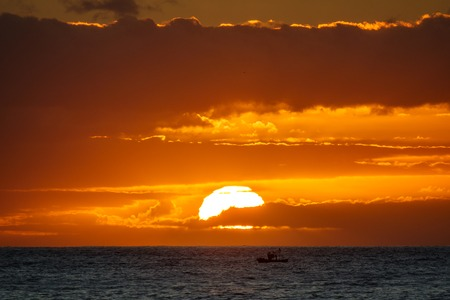Sunset in the ocean with fishing boat Banco de Imagens
