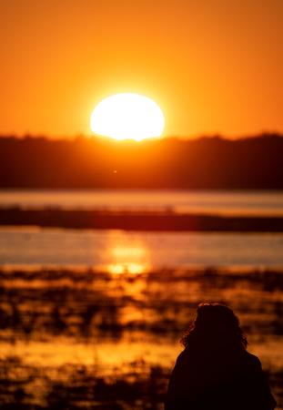 Woman silhouette observing sunrise over the lake Standard-Bild