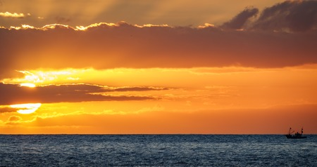 Fishing boat saling to the sun in the horizon at sunset Stock Photo