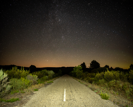 Old road in the bush at night illuminated under the stars