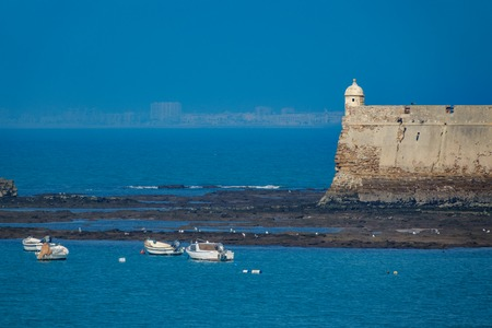 Cadiz fort near ocean in a misty day with blurred city
