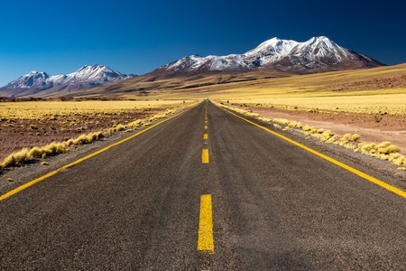Atacama straight road and snow covered volcanoes