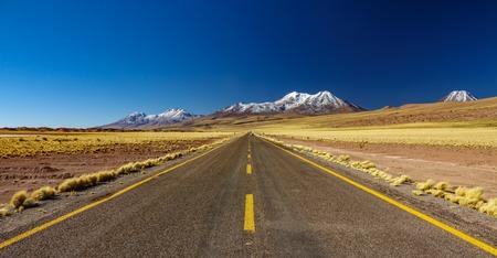 Atacama straight road against snow covered volcanoes Stockfoto - 122142703