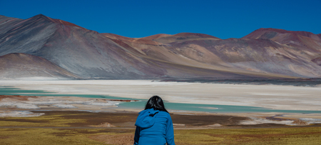 An unidentified tourist observes red stones and Talar salar