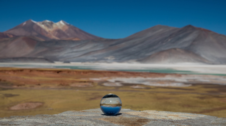 Glass ball at red stones and Talar salar viewpoint Reklamní fotografie