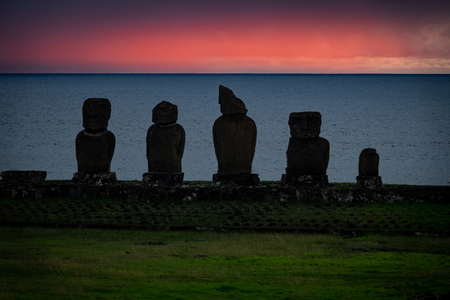 Moai shilouettes in the Ahu Tahai at sunset against pink sky