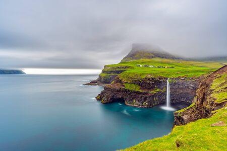 Gasadalur waterfall long exposure in Faroe Islands, misty day