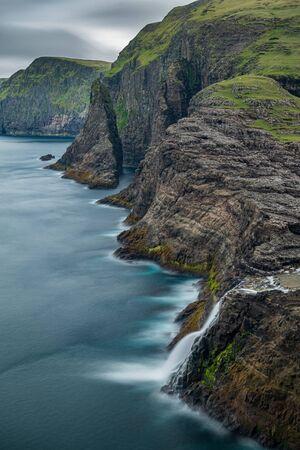 Bosdalafossur waterfall and coastline long exposure, vertical composition in Faroe Islands Stockfoto