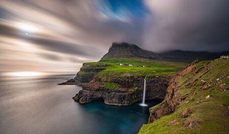 Gasadalur waterfall wide long exposure in Faroe Islands, misty day Stockfoto