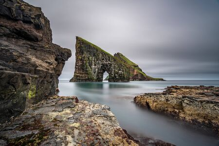 Amazing ultra wide angle long exposure of Drangarnir gate in front of Tindholmur, Faroe Islands Archivio Fotografico - 129488244