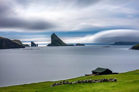 Amazing long exposure of Drangarnir gate, Tindholmur and typical house in Faroe Islands 写真素材