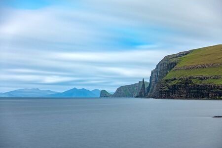 Sandoy rock needle in the steep coastline, long exposure