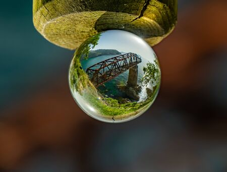 Old abandoned rusty iron loading bay through crystal ball 写真素材