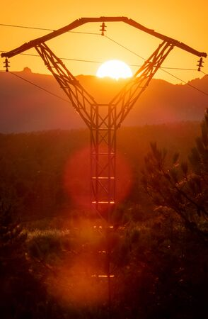 High voltage tower against sunset with light beams Reklamní fotografie