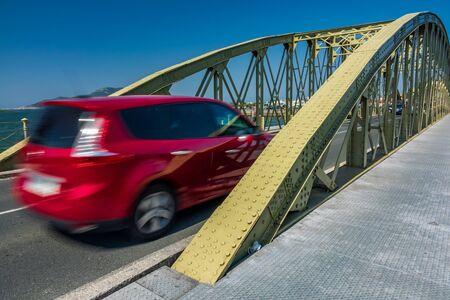 Blurred red car entering vintage iron bridge