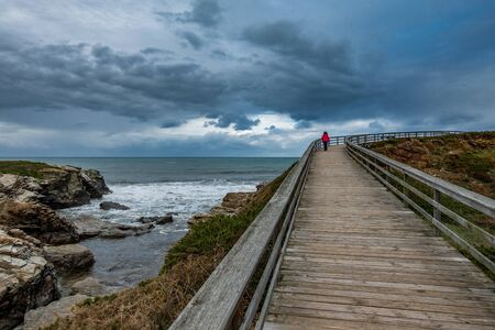 Wooden track through the ocean with hiker