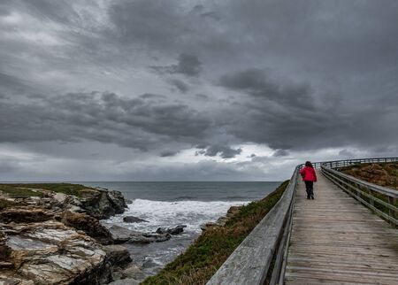 Wooden track through the ocean with hiker under gray sky