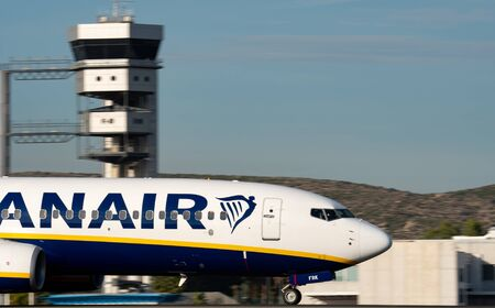 Ryanair plane landing panning with control tower in the background Editorial
