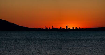 Sunset over Benidorm city skyline and sea in Alicante Imagens