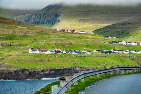 Faroe Islands typical village near the ocean with road