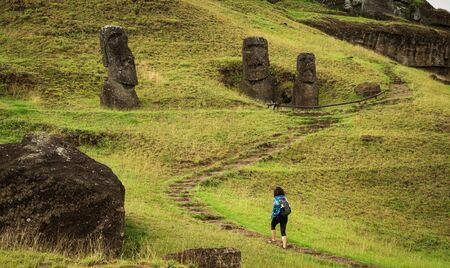 Unrecognizable tourist woman hiking along moais in rpa nui Imagens