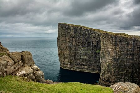 Sorvagsvatn lake huge cliffs over the ocean with small tourists hiking in Vagar island, Faroe Islands Imagens