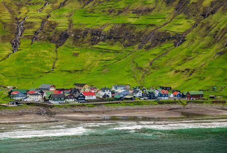 Long shot of Tjornuvik village in the bay under the hillside Imagens