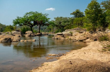 River with rocks and trees under blue sky in Malawi
