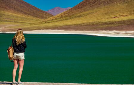 Rear view of unrecognizable tourist woman in the highlands lakes of Atacama