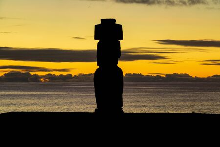Sunset over Easter Island with Moai silhouette and ocean in the background Imagens