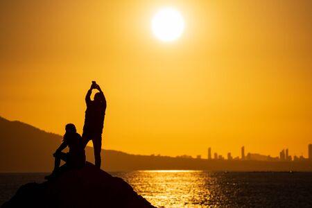 Couple taking photos at sunset over city skyline Stock Photo