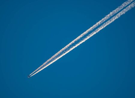 Jet plane trail crosses the sky from top right to bottom left