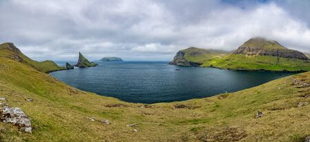 Amazing wide view of Drangarnir gate, Tindholmur and Mykines, Faroe Islands Stock Photo