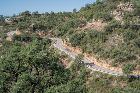 Isolated group of cyclists climbing mountain curved road