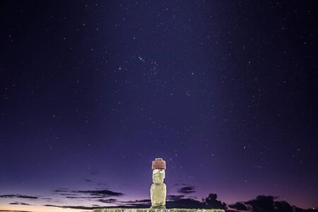 Single moai at night with stars in the sky
